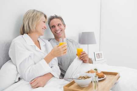 Cheerful couple having orange juice at breakfast in bed at home in bedroom photo