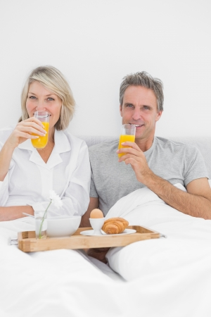 Couple having orange juice at breakfast in bed at home in bedroom photo