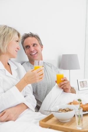 Smiling couple having orange juice at breakfast in bed at home in bedroom photo