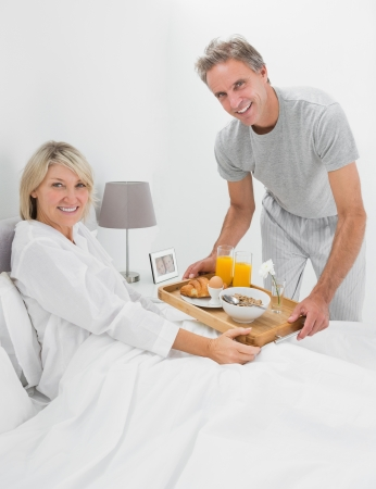 Happy man giving breakfast in bed to his partner smiling at camera photo
