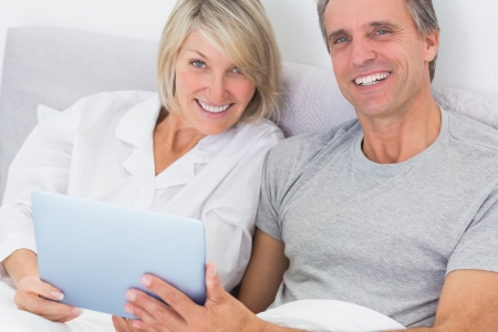 Couple using tablet pc in bed smiling at camera at home in bedroom photo