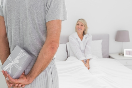 Man hiding present behind his back for partner sitting in bed at home photo