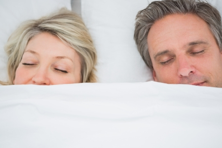 Couple sleeping under the covers at home in bed photo