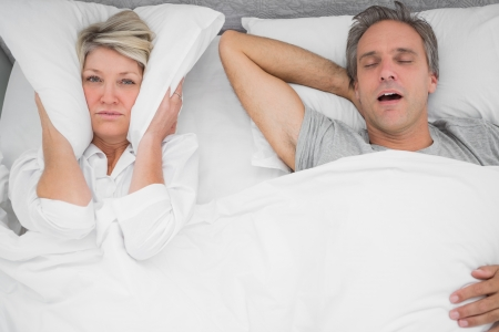 loudly: Man snoring loudly as partner blocks her ears at home in bedroom Stock Photo