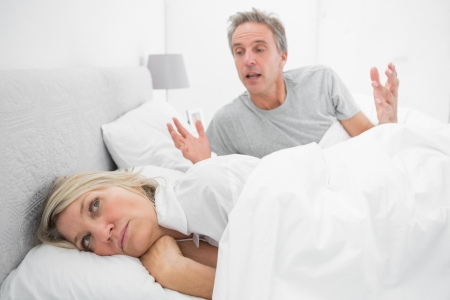Man arguing with his partner in bed at home in bedroom photo