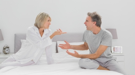 Couple arguing in bedroom sitting on bed photo