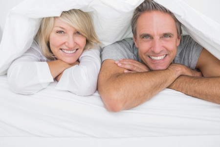 Cheerful couple smiling under the covers at the camera at home in bed photo