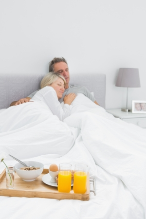 Couple sleeping with breakfast tray at end of bed at home in bedroom photo
