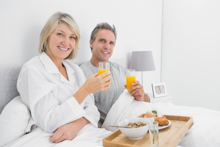 Happy couple having orange juice at breakfast in bed looking at camera photo