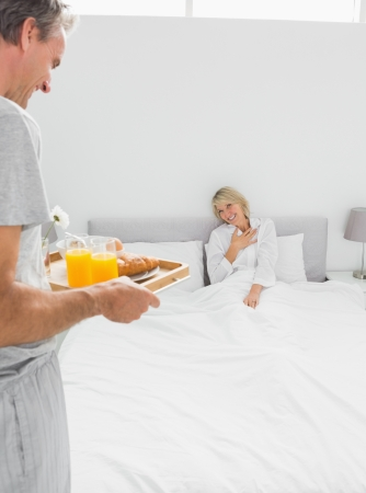 Man bringing breakfast in bed to his surprised partner at home in bedroom photo