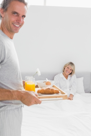 Smiling man bringing breakfast in bed to his partner at home in bed photo