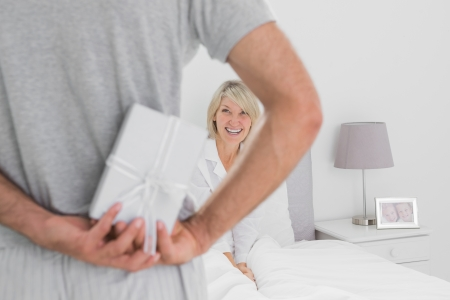 Man hiding present behind his back for smiling partner sitting in bed photo