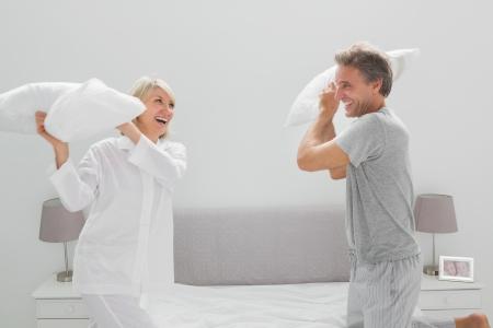 pareja en la cama: Pares que tienen una pelea de almohadas en casa en el dormitorio