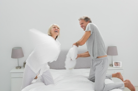 Fun couple having a pillow fight at home in bedroom photo