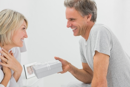 bringing: Man giving present to his pleased partner at home in bedroom Stock Photo