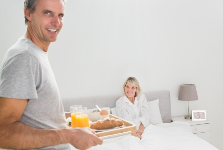 spoiling: Cheerful man bringing breakfast in bed to his partner at home in bedroom