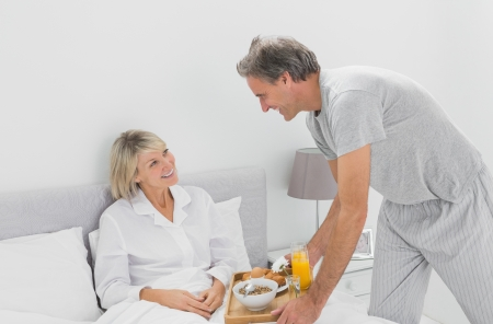 Caring man bringing breakfast in bed to his partner at home in bed photo