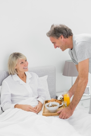 bringing: Considerate man bringing breakfast in bed to his partner at home in bedroom