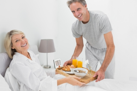 Considerate man giving breakfast in bed to his partner smiling at camera photo