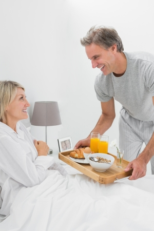 Smiling man giving breakfast in bed to his partner at home in bedroom photo