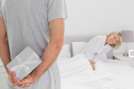 Woman sitting in bed trying to see gift behind partners backtrying  photo