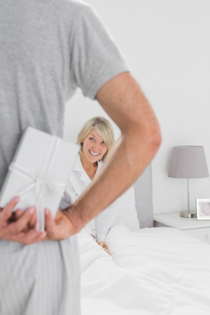 Man hiding present behind his back for happy partner at home in bedroom photo