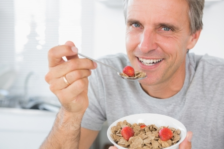 Cheerful man eating cereal for breakfast looking at camera photo