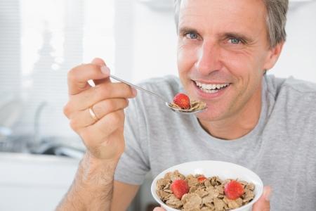 hombre: Hombre alegre comiendo cereales para el desayuno mirando a la cámara