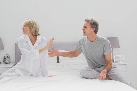 Couple fighting in bedroom at home sitting on bed photo
