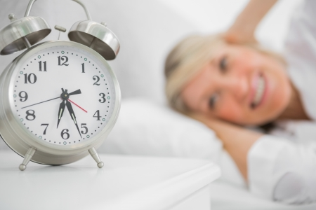 early 40s: Alarm clock annoying blonde woman in bed blocking her ears Stock Photo