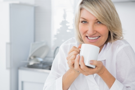 Happy woman having coffee in the morning looking at camera in kitchen photo