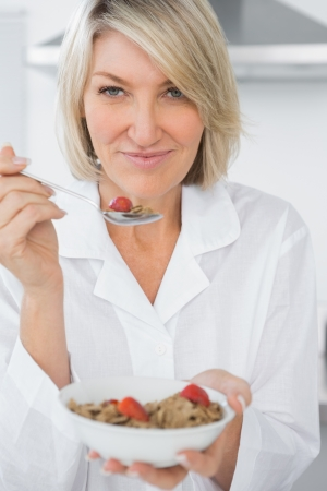 Happy blonde eating cereal for breakfast looking at camera photo