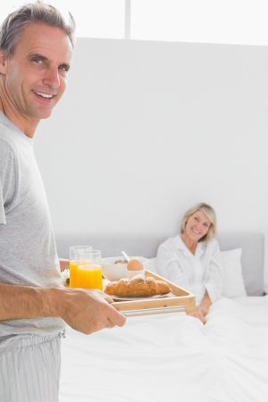 Happy man bringing breakfast in bed to his partner at home in bedroom photo