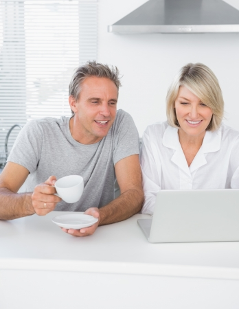 Content couple using laptop in the morning sitting at kitchen counter photo