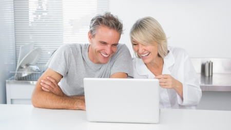Happy couple laughing at laptop in the morning sitting at kitchen counter photo