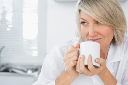 Content woman having coffee in the morning sitting in kitchen at home photo