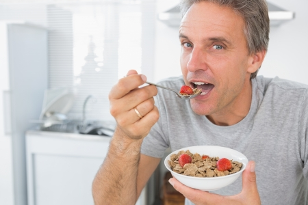 eating breakfast: Happy man eating cereal for breakfast in kitchen looking at camera Stock Photo