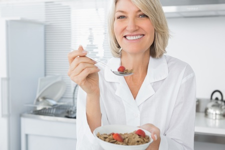 Smiling blonde eating cereal for breakfast looking at camera photo
