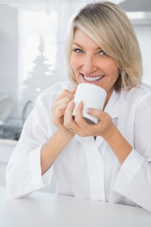 Cheerful woman having coffee in the morning sitting at counter in kitchen photo