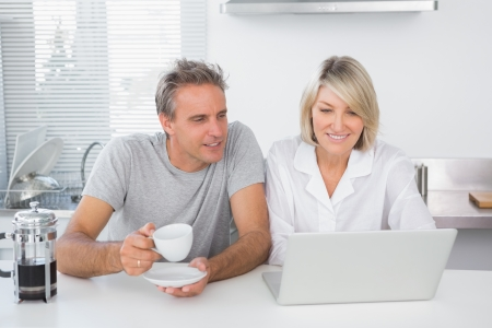 Happy couple using laptop in the morning sitting at kitchen counter photo