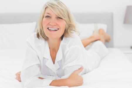 自宅に彼女のベッドに横になっている笑顔の女性はカメラを目線