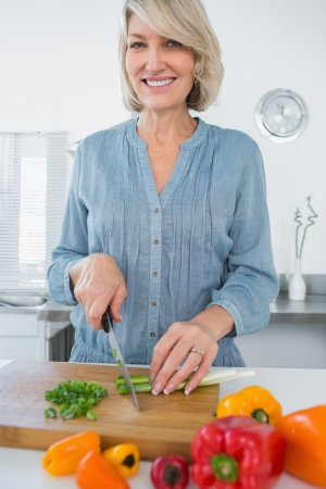 Smiling woman chopping vegetables at the kitchen counter photo