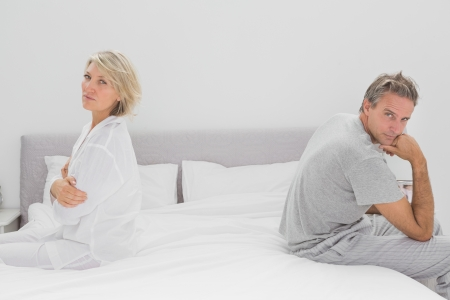 Couple sitting on opposite sides of bed looking at camera after a fight photo