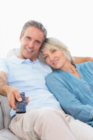 changing channel: Cheerful couple on their couch watching tv at home in living room Stock Photo