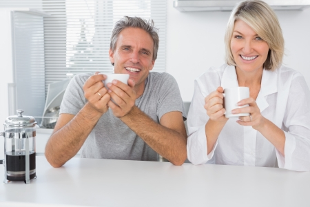 Happy couple having coffee in the morning in kitchen smiling at camera photo