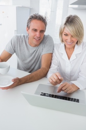 Cheerful couple using laptop in the morning sitting at kitchen counter photo