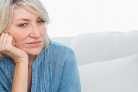 Depressed woman thinking at home on couch photo