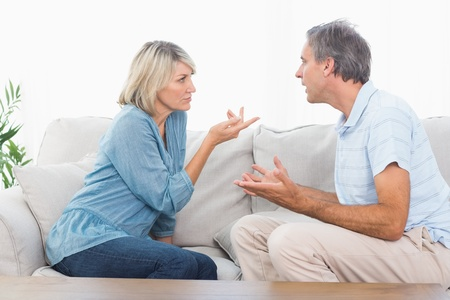 Couple having an argument at home on couch Imagens