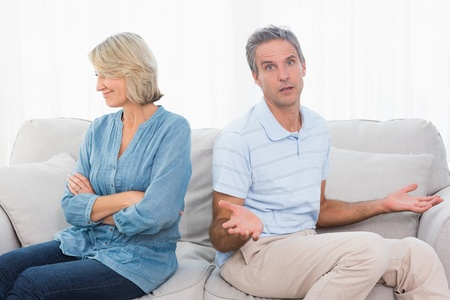 Couple not taking after a fight and man looking confused at camera at home on couch photo