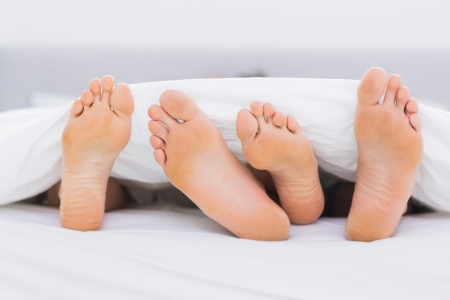 Pair of feet under the covers in a bed photo